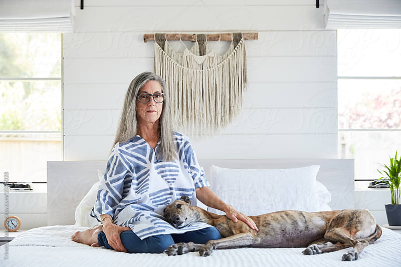 Senior woman with grey hair with her dog at home by Trinette Reed for Stocksy United