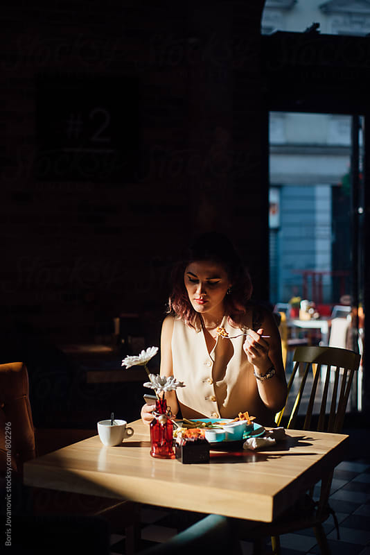 Woman having a breakfast in the restaurant by Boris Jovanovic for Stocksy United