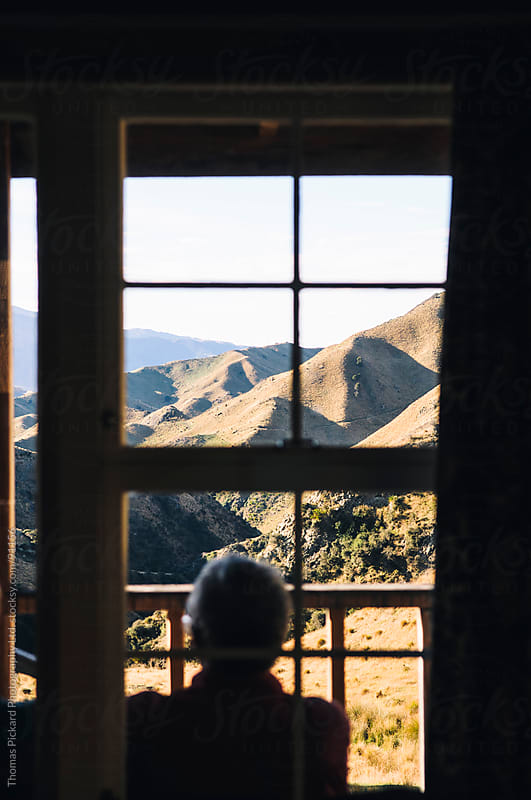 View out of a window over grass covered hills, New Zealand. by Thomas Pickard for Stocksy United
