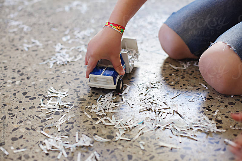Close up of young boy playing with toy truck and pretend snow / shredded paper  by Natalie JEFFCOTT for Stocksy United