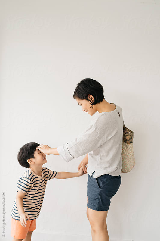 Mother touching her toddler son's face by Alita Ong for Stocksy United