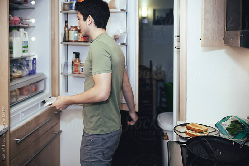 Mexican-American Young Male Student Looking inside Fridge Preparing Breakfast Sandwich by Joselito Briones for Stocksy United