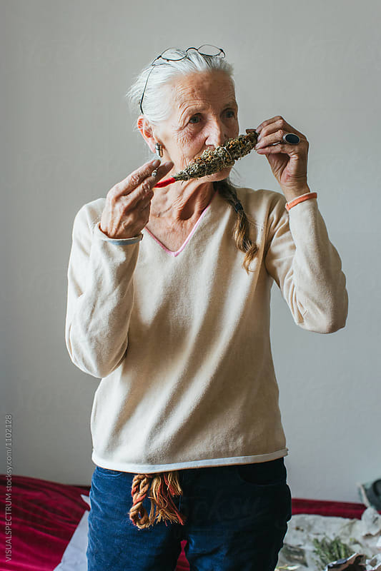 Environmental Portrait of Senior Smoking Woman with Grey Hair Smelling Smudge Stick by Julien L. Balmer for Stocksy United