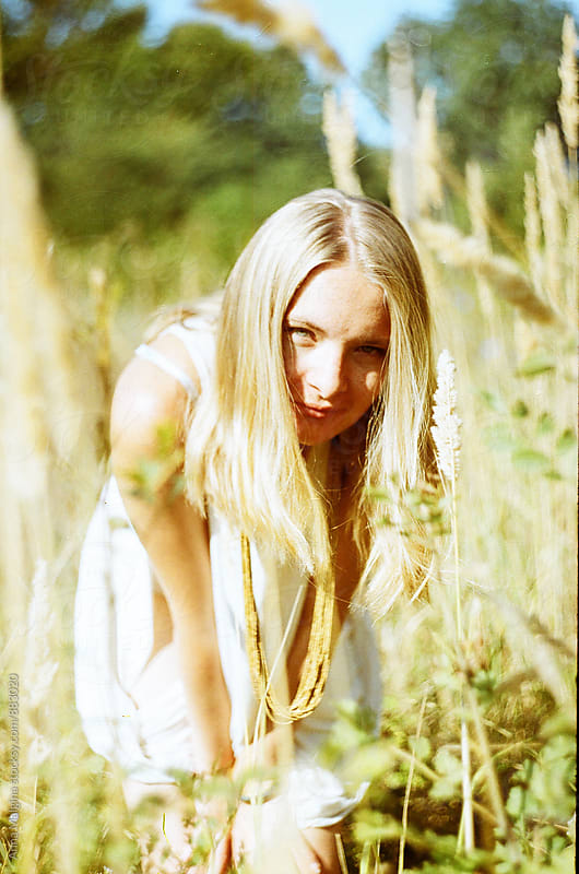 A film portrait of a young blond woman standing in the grass by Anna Malgina for Stocksy United