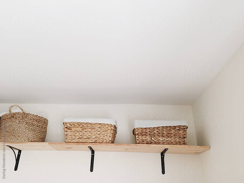 Wicker baskets on shelf by Daring Wanderer for Stocksy United