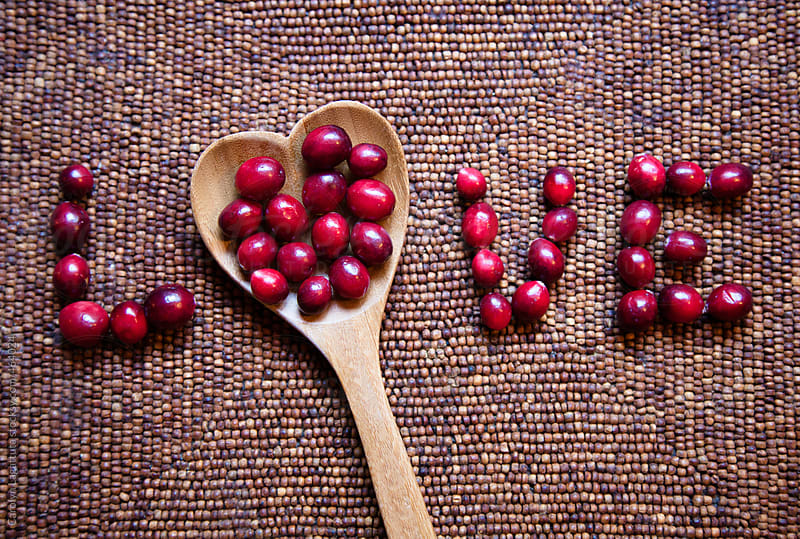 Fresh cranberries and a heart shaped spoon spelling the word LOVE by Carolyn Lagattuta for Stocksy United