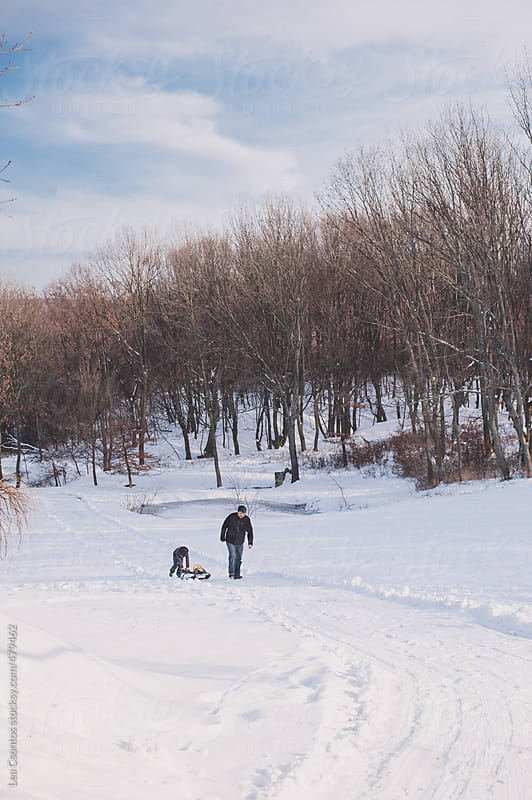 Father and son pulling a sledge up on a snow covered hill by Lea Csontos for Stocksy United