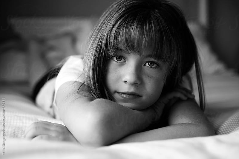 Portrait of Young Girl Laying On Her Bed by Dina Giangregorio for Stocksy United