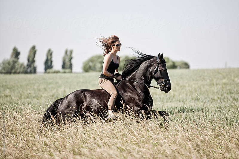 People: Woman riding a black horse in a agrass meadow by Ina Peters for Stocksy United
