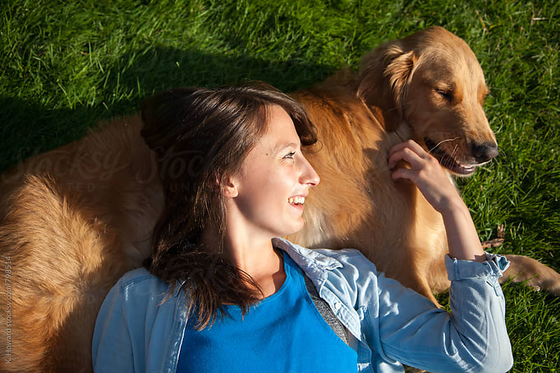 Girl laying with Dog. by K. Howard for Stocksy United