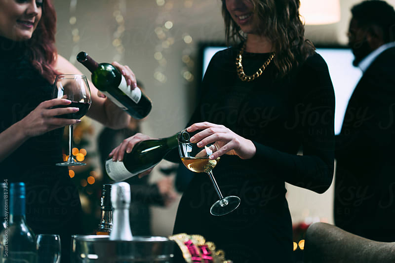 NYE: Friends Getting Wine At Holiday Party by Sean Locke for Stocksy United