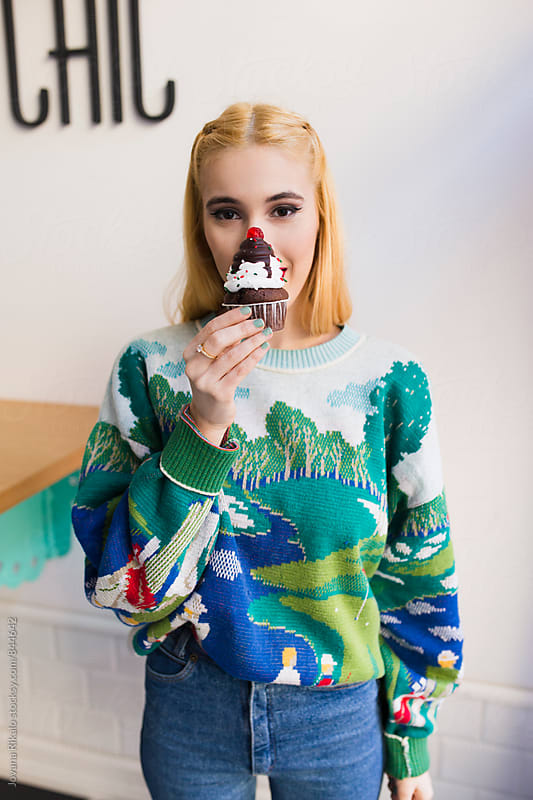 Young woman holding a Christmas cupcake by Jovana Rikalo for Stocksy United