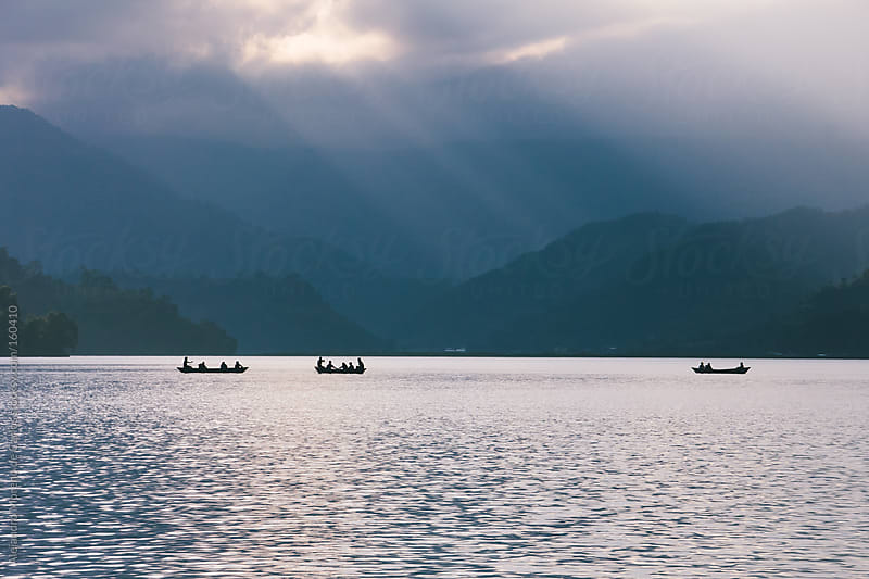 Boats on a lake with light rays and mountains. Travel in Pokhara by Alejandro Moreno de Carlos for Stocksy United
