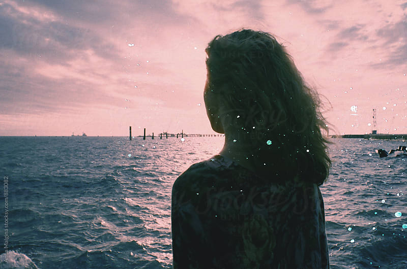 A back portrait of young woman in front of sea made with expired film by Anna Malgina for Stocksy United