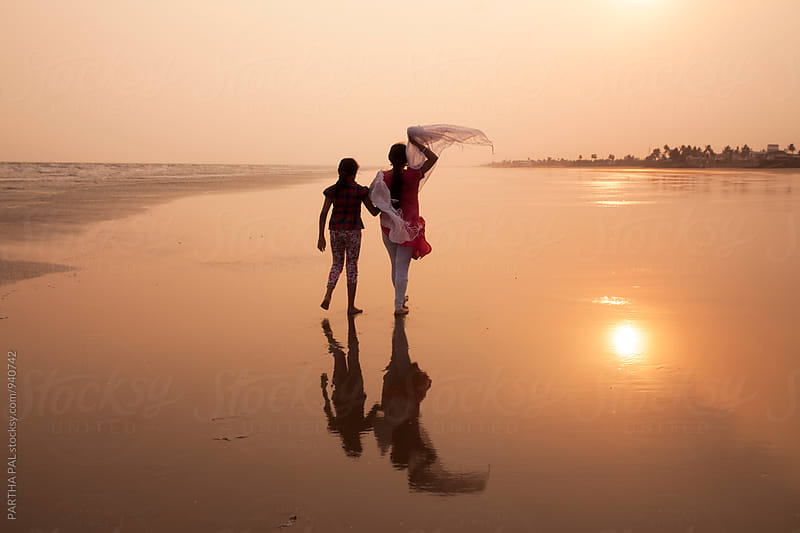 Mother and daughter walking together in the beach by PARTHA PAL for Stocksy United