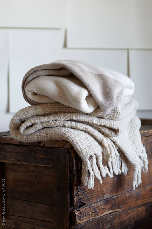 two blankets stacked on top of distressed old wood trunk by Sherry Heck for Stocksy United