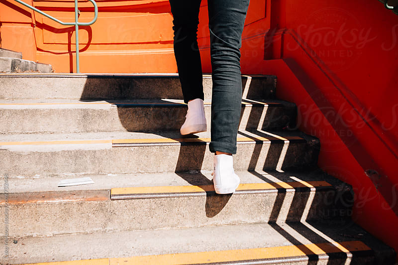 Man Wearing High Top Converse Walking Up Concrete Steps by Luke Mattson for Stocksy United