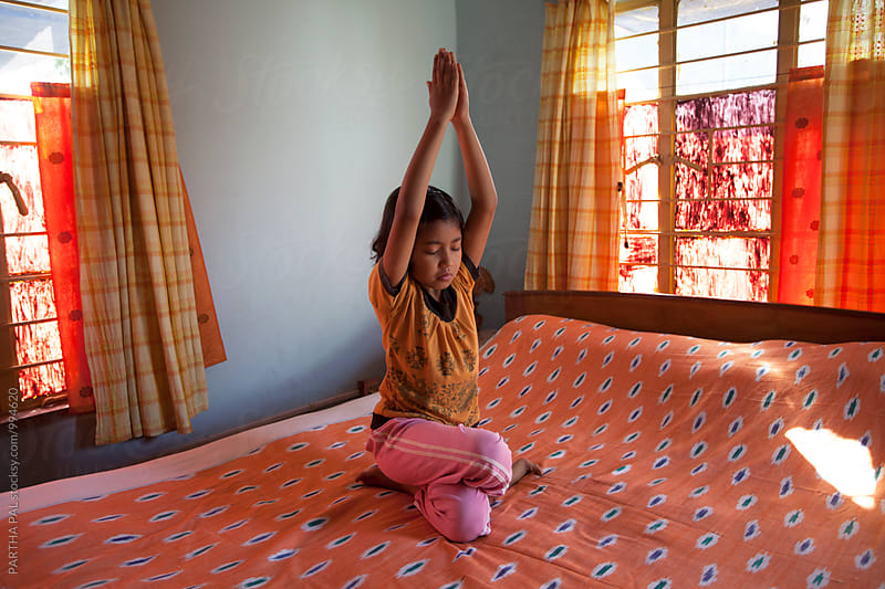 A little girl doing Yoga inside house by PARTHA PAL for Stocksy United