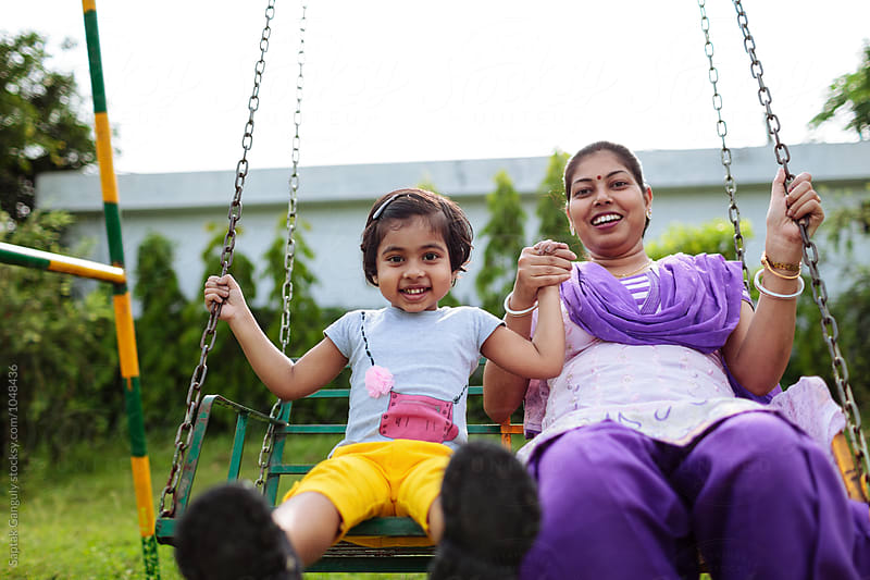 Mother and daughter enjoying outdoors on a swing by Saptak Ganguly for Stocksy United