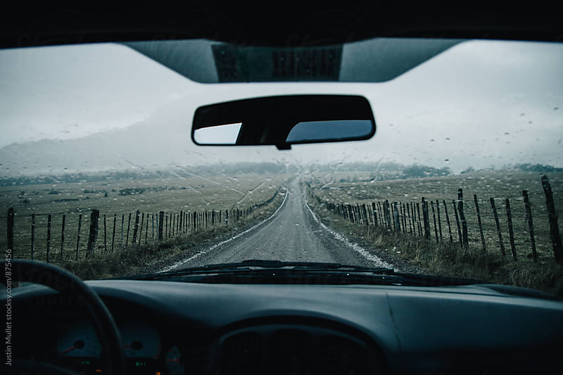 Driver's point of view on a straight narrow road in the country by Justin Mullet for Stocksy United