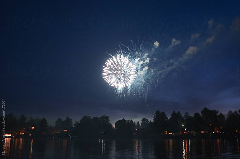 fireworks over a lake by Margaret Vincent for Stocksy United