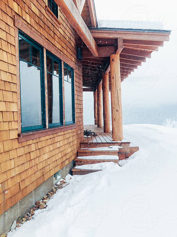 Cedar Shingle Cabin And Porch On Snow Covered Hill In Middle Of Winter by Luke Mattson for Stocksy United