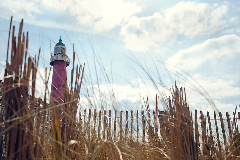 a lighthouse behind the dunes by Denni Van Huis for Stocksy United