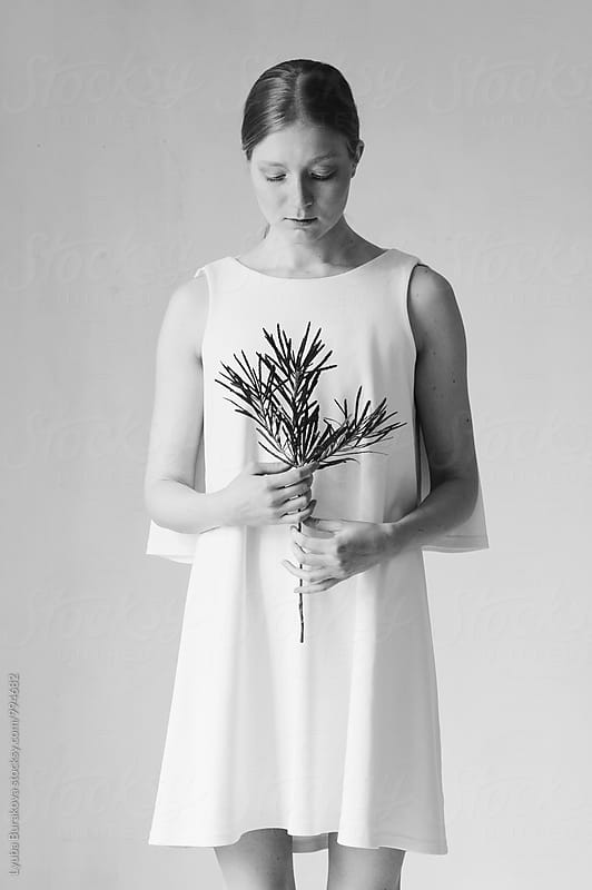 Young woman holding a sprig by Lyuba Burakova for Stocksy United
