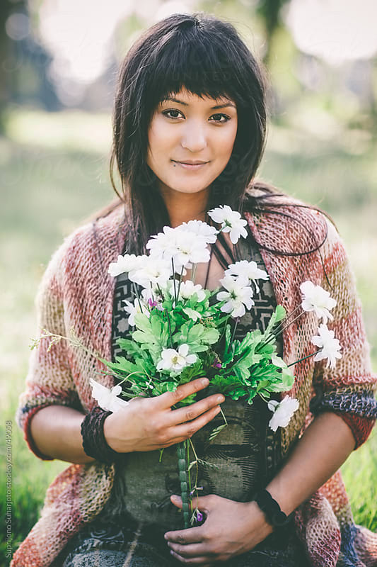 Beautiful woman holding flowers on a grass field by Suprijono Suharjoto for Stocksy United
