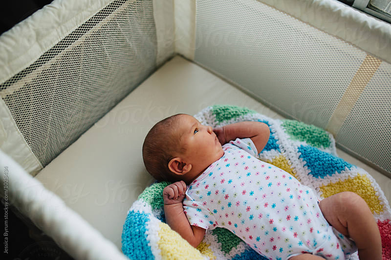 Baby in bassinet looking at window by Jessica Byrum for Stocksy United