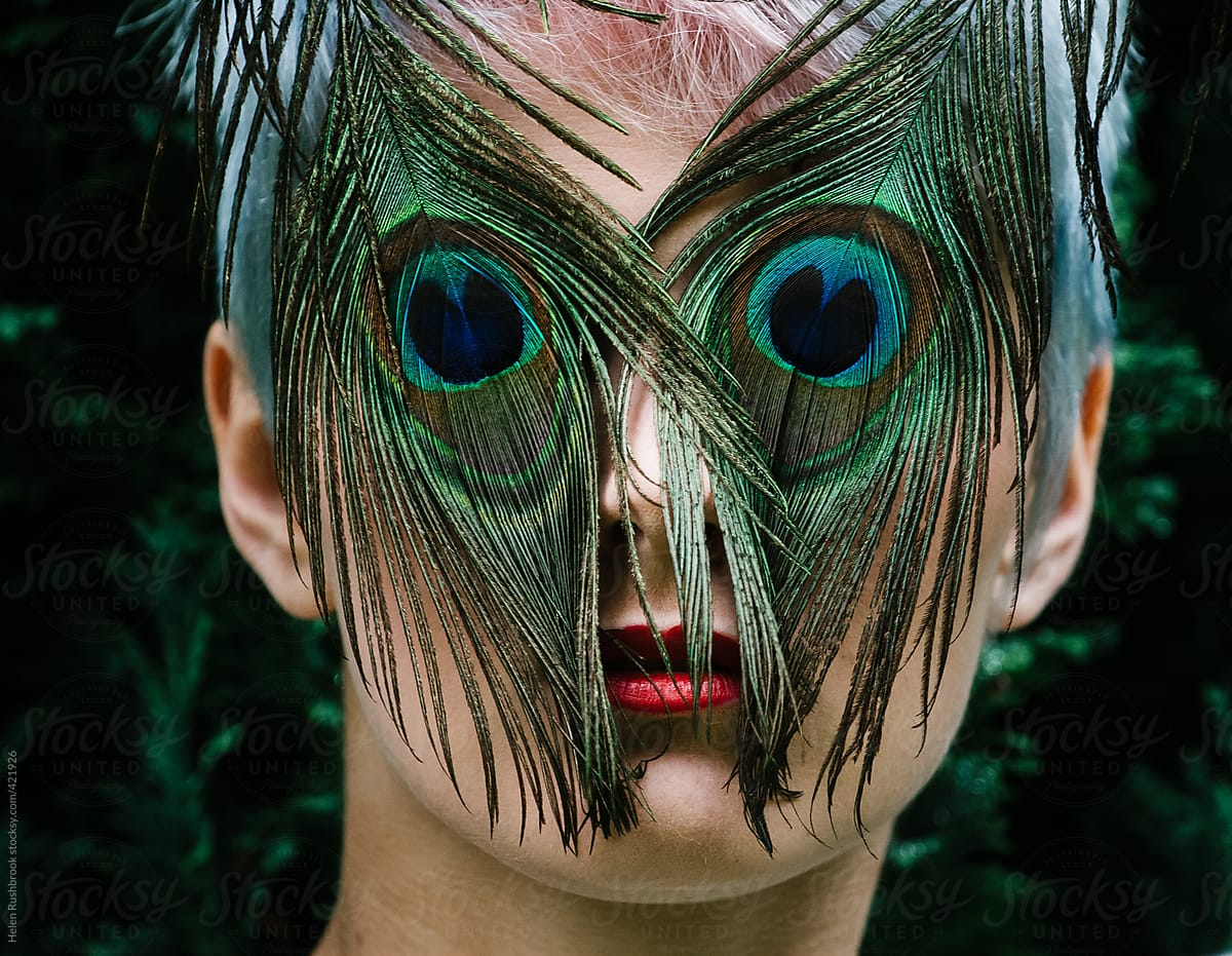 An edgy young woman with a peacock feather mask.