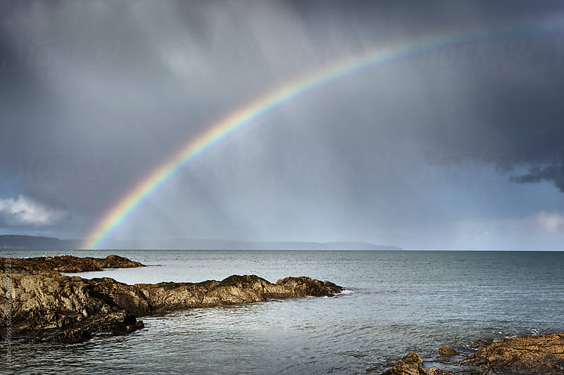 Stormy skies and a rainbow by James Ross for Stocksy United