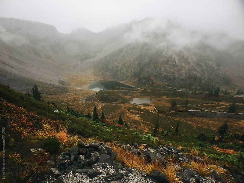 Evergreen Alpine Lakes In Foggy Mountainous Valley by Luke Mattson for Stocksy United