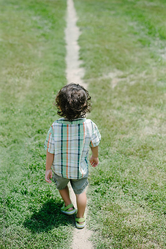 toddler walks away on a straight path by Tara Romasanta for Stocksy United