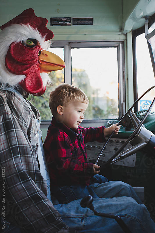 Cute toddler boy in plaid shirt pretending to drive bus with chicken man by Rob and Julia Campbell for Stocksy United