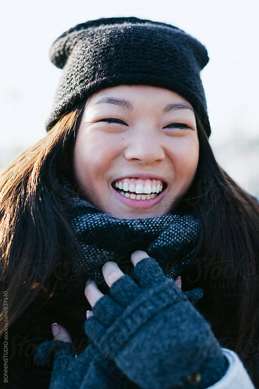Portrait of a woman laughing outside on winter. by BONNINSTUDIO for Stocksy United