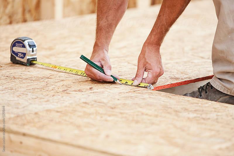 Construction: Framer Making Measurements on MDF Panel by Sean Locke for Stocksy United