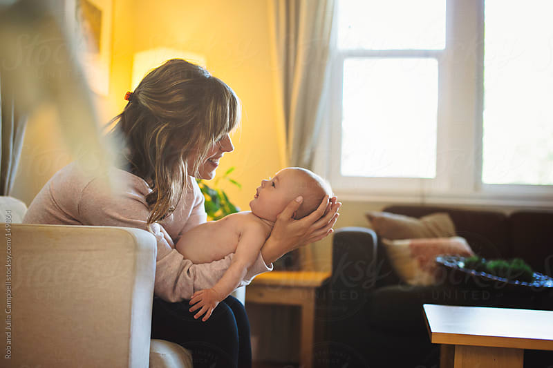 Beautiful young mother holds baby boy by Rob and Julia Campbell for Stocksy United