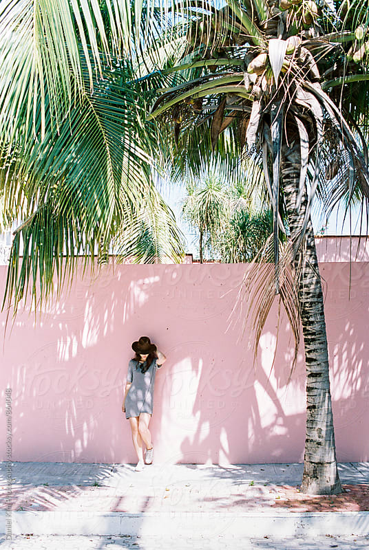 Woman in front of tropical pink wall by Daniel Kim Photography for Stocksy United
