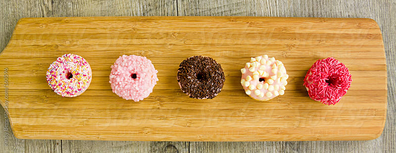 Five iced doughnuts overhead by Kirsty Begg for Stocksy United