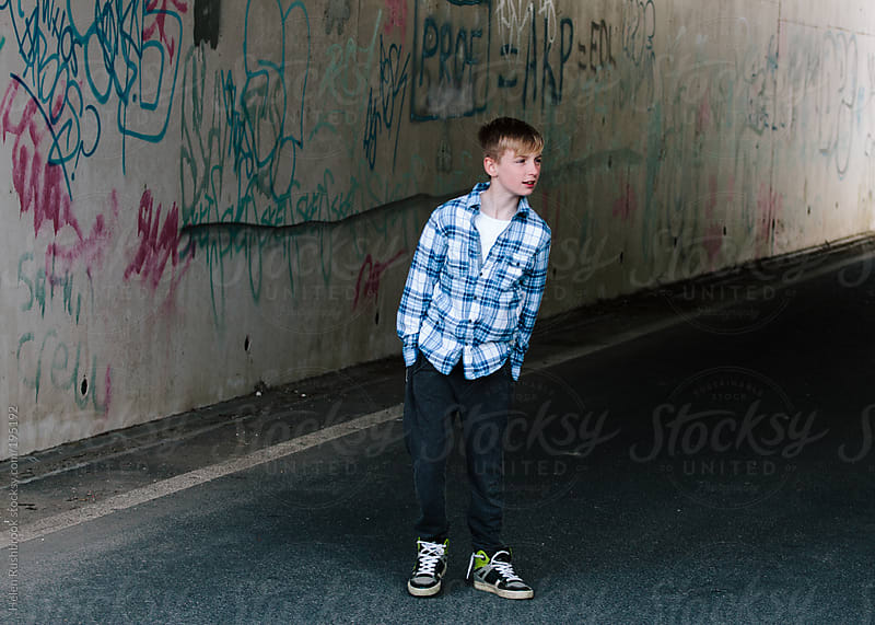 Trendy young boy standing in a heavily graffitied underpass by Helen Rushbrook for Stocksy United