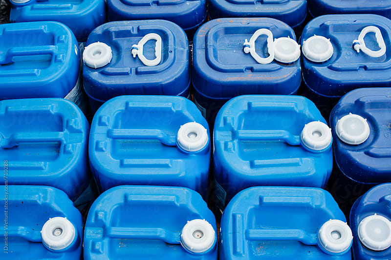 A close up of blue chlorine containers. by J Danielle Wehunt for Stocksy United