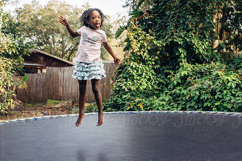 Black girl jumping on trampoline by Gabriel (Gabi) Bucataru for Stocksy United