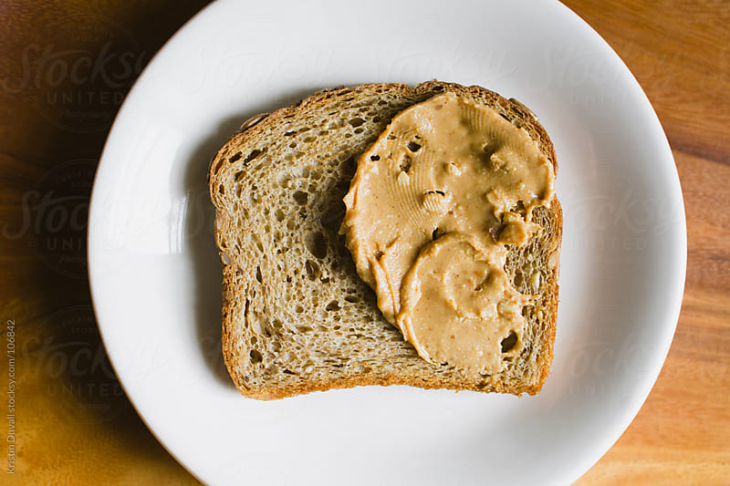 Natural peanut butter on slice of whole grain bread by Kristin Duvall for Stocksy United