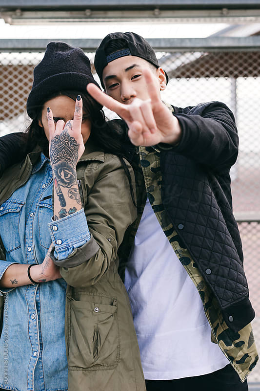 Young alternative couple doing heavy metal sign. by BONNINSTUDIO for Stocksy United