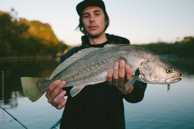 Angler holding Mulloway he just caught by Gary Radler Photography for Stocksy United