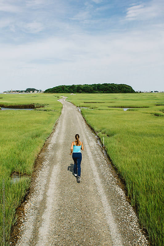 Woman Running Through Marsh by Raymond Forbes LLC for Stocksy United