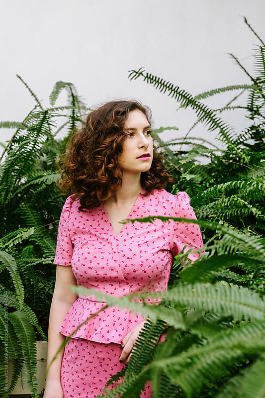 Woman in the Pink Dress Standing Among the Plants in the Greenhouse by Aleksandra Jankovic for Stocksy United