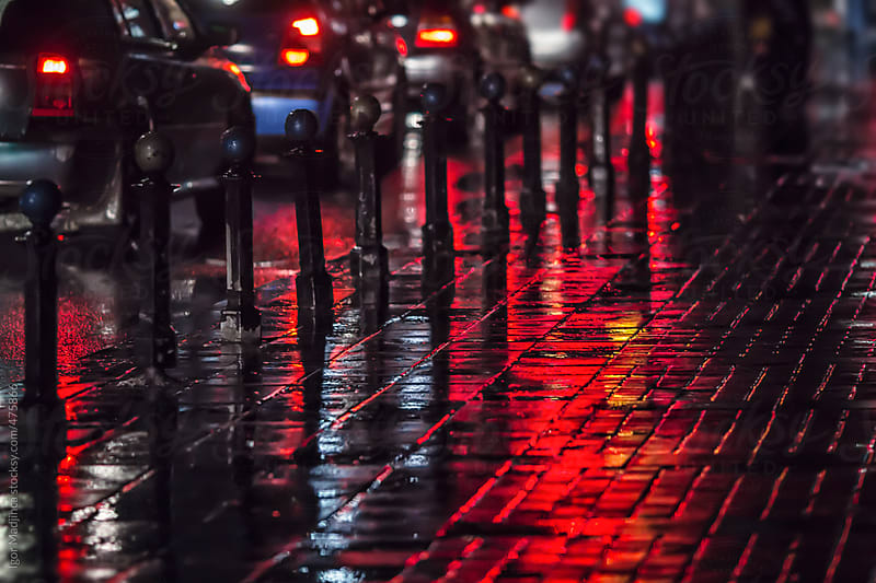 street atmosphere, rain, cars, red reflections, horizontal by Igor Madjinca for Stocksy United