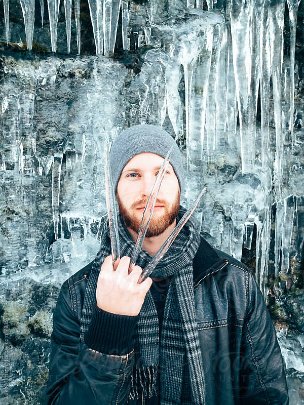 A Young Man Poses As Wolverine With Three Icicles Between His Fingers by Luke Mattson for Stocksy United